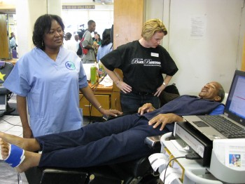 UNAC/UHCP Member Darla Tillman, RN, administers a peripheral arterial disease screening exam to Crenshaw community members to locate any early warning signs for serious medical conditions.
